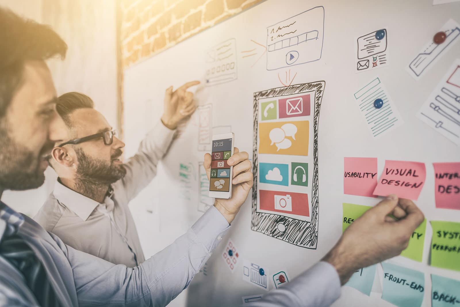 Zwei E-Commerce Experten besprechen das Responsive Design einer Webseite vor einer Tafel.